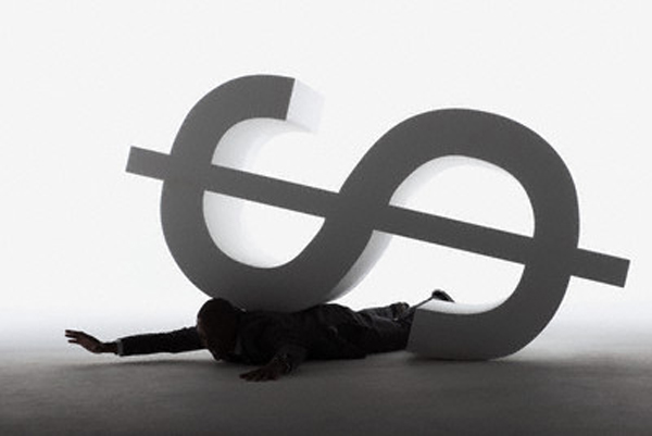 Businessman trapped under a dollar sign --- Image by © Beau Lark/Corbis